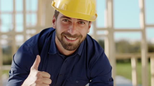 El arquitecto mirando a cámara y mostrando los pulgares para arriba en sitio de construcción - vídeo
