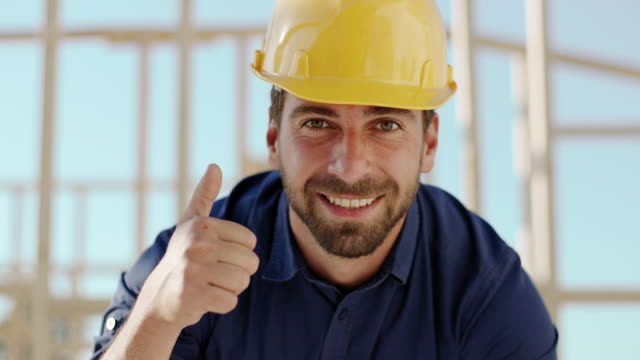 Architect looking at camera and showing thumbs up at construction site video