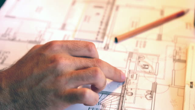 Architect man holding pencil working with laptop and blueprints for architectural plan, engineer sketching a construction project concept. Architect man holding pencil working with laptop and blueprints for architectural plan, engineer sketching a construction project concept. blueprint stock videos & royalty-free footage