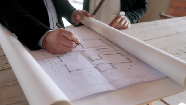 Architect Showing Project Plans To Married Couple In New Building