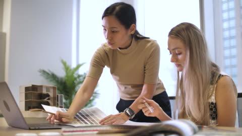 vidéos et rushes de équipe d'architecte utilisant l'ordinateur portatif et examinant des plans au bureau - bureau ameublement