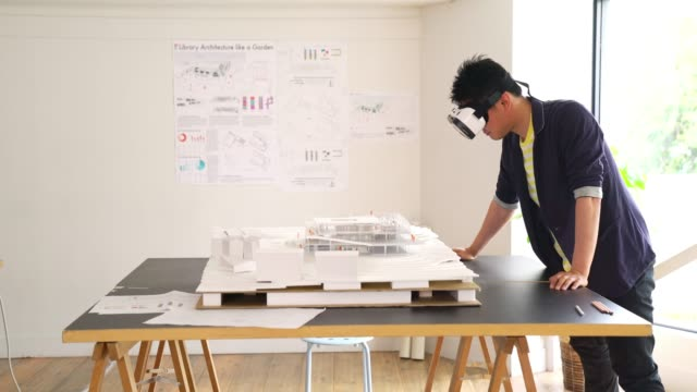 Architect using a VR headset to explore a 3D architectural model видео