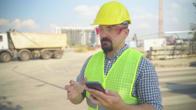 architect using mobile phone on construction site - ispettore della qualità video stock e b–roll