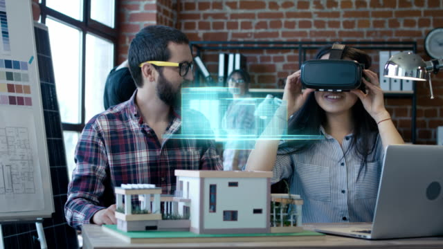 Architect using VR headset for presentation Medium shot of an architect presenting house plan to client by virtual reality hologram stock videos & royalty-free footage