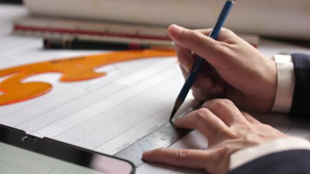 建築計画のためのラップトップと青写真で作業鉛筆を保持する建築家の女性 - 図面点の映像素材/bロール