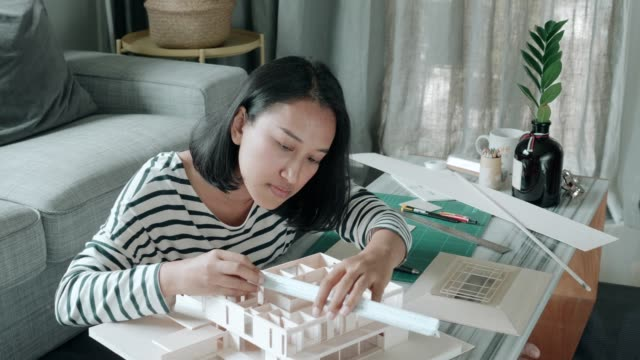 Architect woman using scale for making her model home