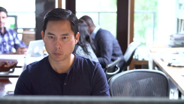Architect Working At Desk With Meeting In Background video