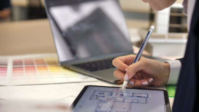 Architect Working on House Blueprint plan with Tablet PC