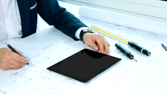 Architect working on table with digital tablet video