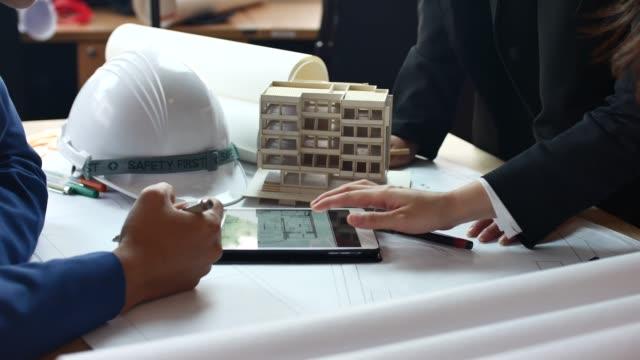 arkitekter och ingenjörer möte och diskussion på ritningar på byggarbetsplats - man architect computer bildbanksvideor och videomaterial från bakom kulisserna