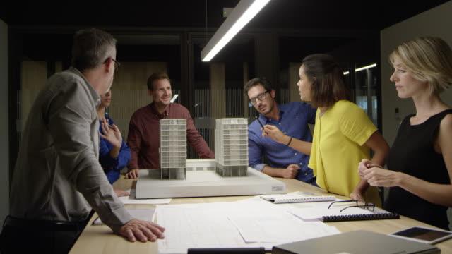 vídeos y material grabado en eventos de stock de arquitectos discutiendo sobre construcción de modelo en la mesa - arquitecto