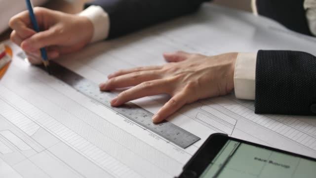 テーブルで議論する建築家エンジニア - 図面点の映像素材/bロール