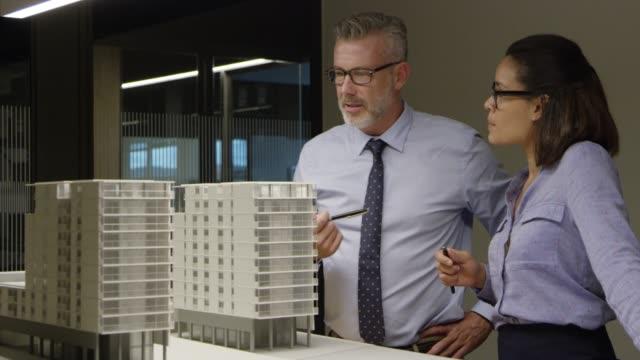vídeos y material grabado en eventos de stock de arquitectos que examinan la construcción de modelos en oficina - arquitecto
