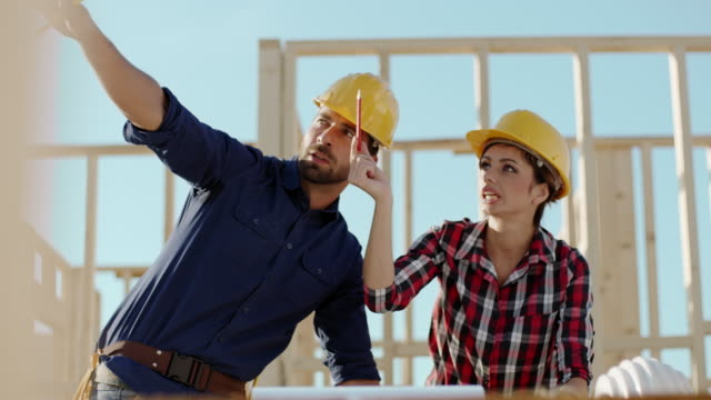 Architects reviewing blueprints on construction site and inspecting building video
