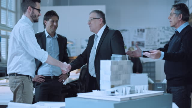 DS Architects shaking hands with investor next to the design model video