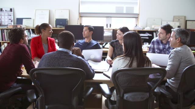 architects sitting around table having meeting - fritidskläder bildbanksvideor och videomaterial från bakom kulisserna