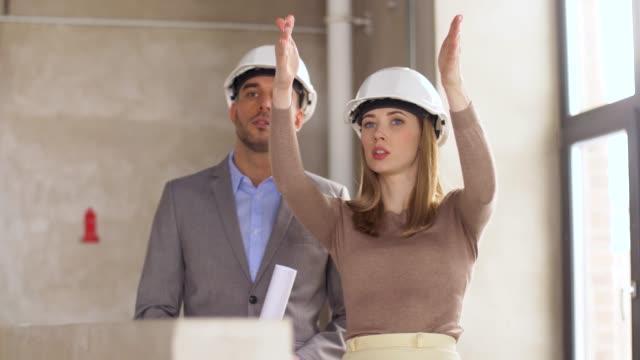 vídeos de stock, filmes e b-roll de arquitetos com planta e capacetes no escritório - sul europeu