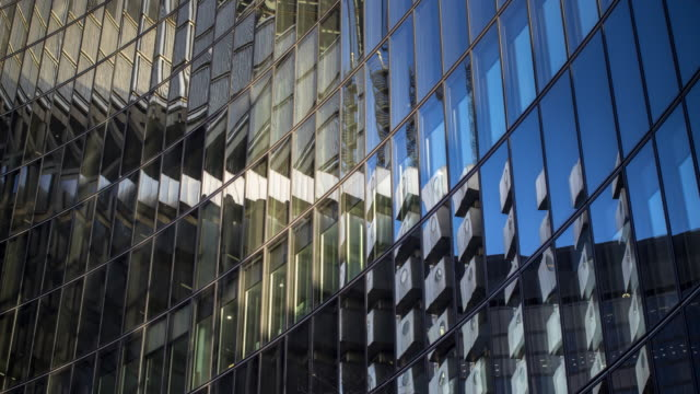 Architectural Abstract of Modern Office Building - Time Lapse Time lapse shot of a curved glass building reflecting the surrounding buildings, moving clouds and changing sunlight. london architecture stock videos & royalty-free footage
