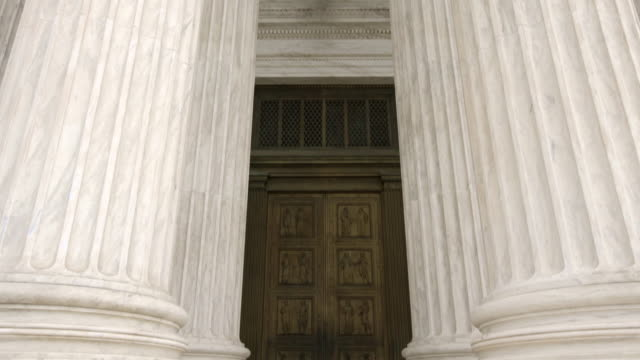 Architectural Columns and Doors of the Supreme Court of the United States in Washington, DC Architectural Columns in front of the United States Supreme Court in Washington DC - Tilt Down supreme court stock videos & royalty-free footage