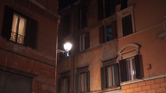 stockvideo's en b-roll-footage met architectonische decoraties op oude romeinse straten 's nachts. traditionele gebouw exterieur, knipperend licht in windows, oude romeinse lampen opknoping en verlichtende weg in de avond. historisch monument, het machtige romeinse rijk en zijn architectuur - raam bezoek