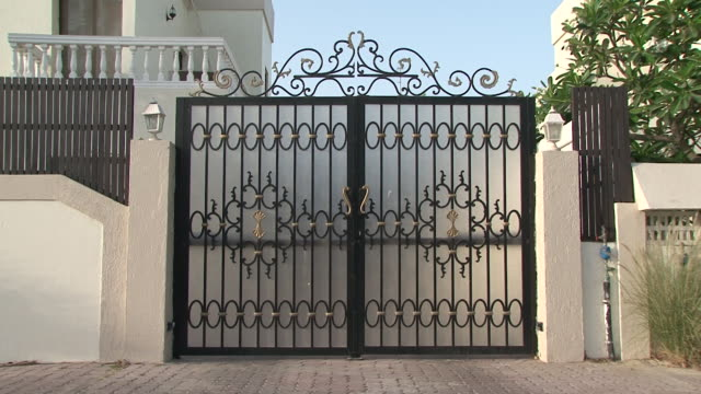 Architecture, Dubai Residential architecture, Dubai. View of an ornate gate with rococo wrought iron details. wrought iron stock videos & royalty-free footage