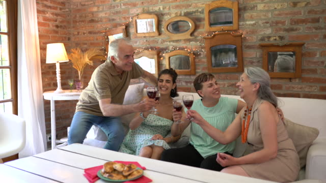Argentian family toasting  wine glasses  and eating empanada at home
