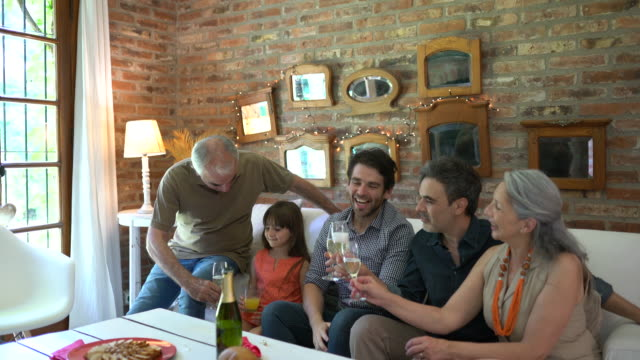 Argentian family toasting  wine glasses  and eating empanadas at home