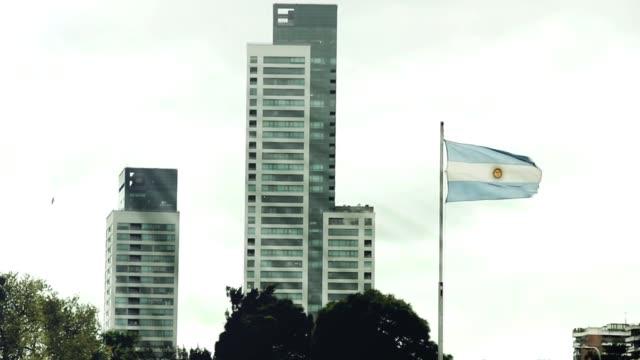 Bandera de Argentina y los edificios de Buenos Aires (Argentina). - vídeo