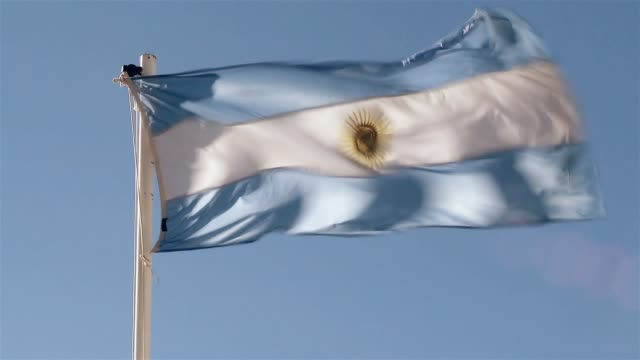 argentina flag on blue sky. - bandiera dell'argentina video stock e b–roll