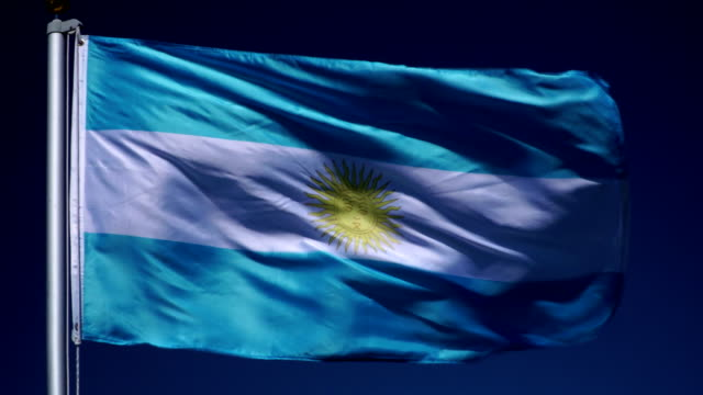 4k: argentinian flag on flagpole in front of blue sky outdoors (argentina) - bandiera dell'argentina video stock e b–roll
