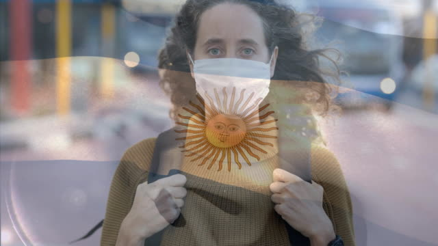 argentinian flag waving against woman wearing face mask - bandiera dell'argentina video stock e b–roll