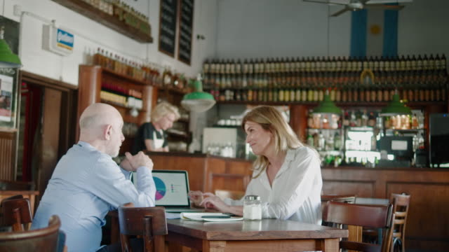 Argentinian senior businessman and businesswoman having a meeting in the restaurant