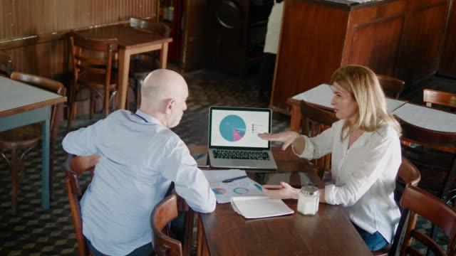 Argentinian senior businessman and businesswoman having a meeting during lunch break in restaurant