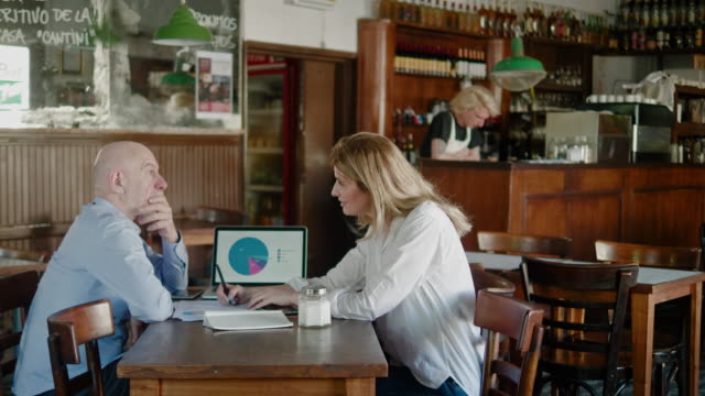 Argentinian senior businessman and businesswoman planning small business in the restaurant
