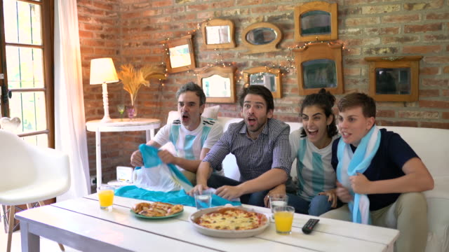 Argentinian soccer fans  cheerful, screaming eating takeaway pizza  and looking soccer play
