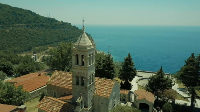 arial view. Catholic cathedral in small town, a church of white stone on the seashore summer video