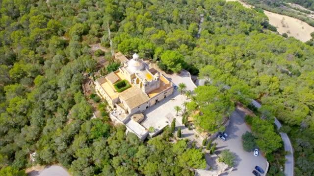 stockvideo's en b-roll-footage met arial weergave van ermita de nostra senyora de bonany in de buurt van door vilafranca de bonany, berg met klooster op mallorca / spanje - klooster