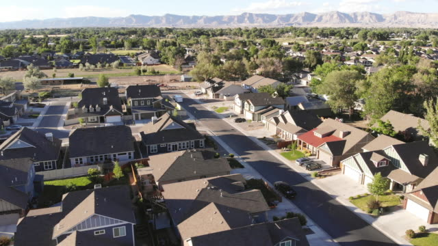 Ariel View of Neighborhood Street Lined with Homes on a Sunny Summer Day Ariel View of Neighborhood Street Lined with Homes on a Sunny Summer Day (Drone Video Shot 4K rendered DaVinci Resolve 24 FPS second clips) house aerial stock videos & royalty-free footage