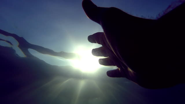arm asking for help and trying to reach to the sun. point of view of man drowning in the sea or ocean and floating to the surface. male hand stretches from under the water to sun rays. close up - погружённый стоковые видео и кадры b-roll