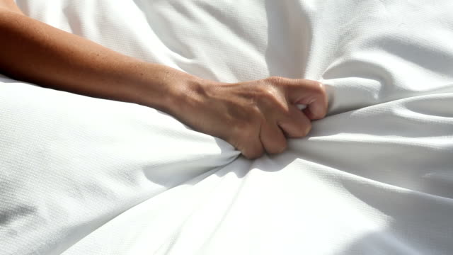 arm of woman grabbing a white blanket in bed and relaxes - human sexual behavior stock videos & royalty-free footage