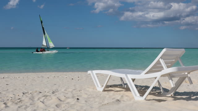Armchair on Tropical Beach, Cayo Coco Cuba 4K UHD Video of Armchair on Tropical Beach, Cayo Coco Cuba. There is a Sailboat in the background. lounge chair stock videos & royalty-free footage