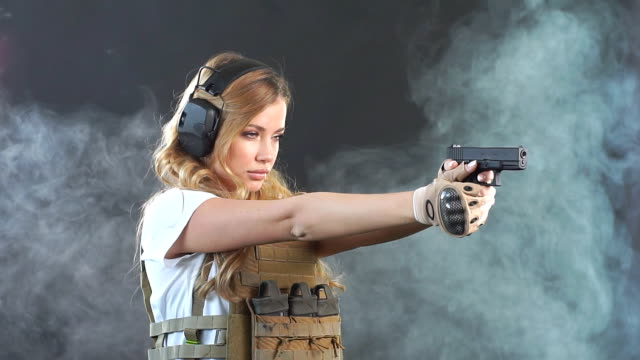 Armed blonde woman shoots with gun at a target in the darkness with smoke clouds. Slow motion