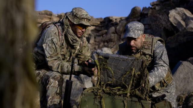 vídeos de stock e filmes b-roll de armed soldiers looking at a computer - fuzileiro naval