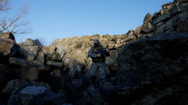 vídeos de stock e filmes b-roll de armed soldiers walking over large rocks - fuzileiro naval