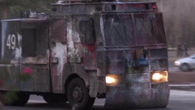 vídeos de stock, filmes e b-roll de caminhão blindado da polícia pulverizaágua água em manifestantes nas ruas de santiago, chile - domínio