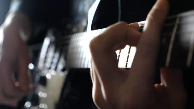 braccia di musicista maschio che suona con la chitarra elettrica. chiudi le dita del chitarrista che impicca le corde. mani di ragazzo che si esibisce da solo di musica rock. l'uomo adulto suona su uno strumento musicale. rallentatore - braccio umano video stock e b–roll