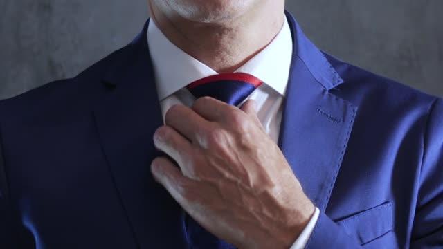 vídeos y material grabado en eventos de stock de brazos de la persona en traje azul se endereza corbata en cuello sobre fondo de pared concreto gris - corbata