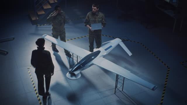 vidéos et rushes de les ingénieurs aérospatiaux de l'armée travaillent sur un véhicule aérien sans pilote/drone. les experts de l'aviation en uniforme parlent, utilisant l'ordinateur portable. installation industrielle avec des aéronefs pour effectuer la surveilla - armement