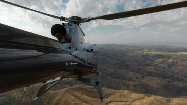 vídeos de stock, filmes e b-roll de um helicóptero do exército americano sobrevoa as montanhas no afeganistão. vista da cauda do helicóptero em 4k - helicóptero