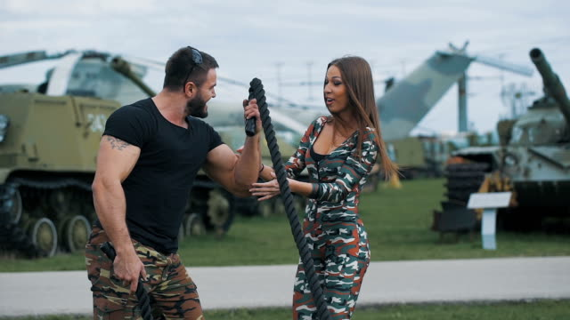 Army man and a woman in a romantic relationship Army man and a woman in a romantic relationship. She admires the size of the biceps of her friend. Around military equipment military lifestyle stock videos & royalty-free footage